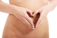 Feamle's flat belly with heart hand shape. Isolated on white Stock Images