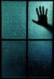 Fear. Silhouette of a hand behind a window or glass door (symbolizing horror or fear royalty free stock images