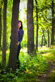 Fear. Girl hide behind tree in forest Stock Images