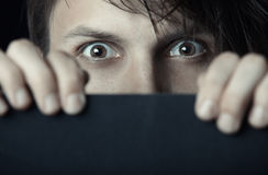 Fear. Afraid man hiding behind the black board Stock Images