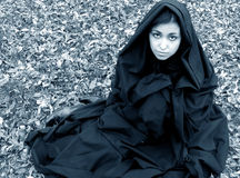 Fear. Beautiful woman sited on a carpet of fallen leaves dressed in a black cap with hood, medieval look royalty free stock photo