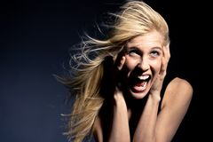 Fear. Young blond woman screaming in fear, studio stock photos