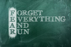 Fear acronym. Forget everything and run - FEAR acronym on green chalkboard Royalty Free Stock Photos