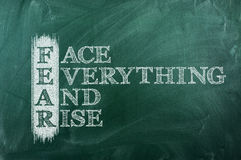 Fear acronym positive. Face everything and rise - FEAR acronym on green chalkboard stock photo