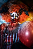 Fear balloons. Evil redhead clown stained in blood holding balloons. Female zombie clown. Halloween. Horror Royalty Free Stock Photos