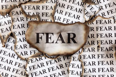 Fear. Burnt Fear. Burnt pieces of paper with the word Fear. Close-up royalty free stock photography