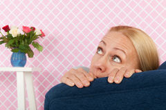Fear in the chair. Middle aged woman having fear in the living room royalty free stock photo