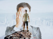 Fear of failure concept. Businessman covering face on abstract background with casual guy standing on mountain top. Fear of failure concept. Double exposure royalty free stock photos