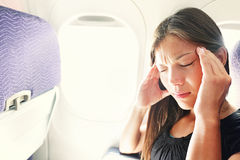 Fear of flying woman in plane airsick. With stress headache and motion sickness or airsickness. Person in airplane with aerophobia scared of flying being afraid stock image