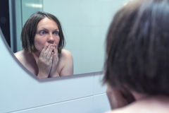 Fear of getting old, adult female in front of mirror Stock Images
