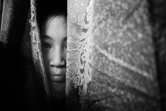 Fear girl hiding behind curtain with shadow edge. Fear girl hiding behind curtain in white tone with shadow edge royalty free stock images