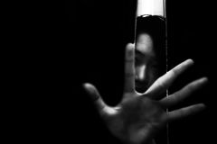 Fear girl hiding in closet with hand reaching out. In white tone stock photos