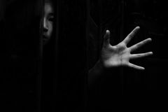 Fear girl hiding in closet with hand reaching out. In white tone stock images