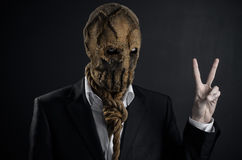 Fear and Halloween theme: a brutal killer in a mask on a dark background in the studio Royalty Free Stock Photo