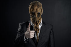 Fear and Halloween theme: a brutal killer in a mask on a dark background in the studio Stock Photo