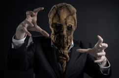 Fear and Halloween theme: a brutal killer in a mask on a dark background in the studio. Fear and Halloween theme: a brutal killer in a mask on a dark background Royalty Free Stock Photo