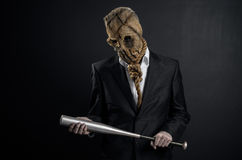 Fear and Halloween theme: a brutal killer in a mask holding a bat on a dark background in the studio. Fear and Halloween theme: a brutal killer in a mask holding Stock Image