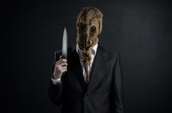 Fear and Halloween theme: a brutal killer in a mask holding a knife on a dark background in the studio Royalty Free Stock Photo
