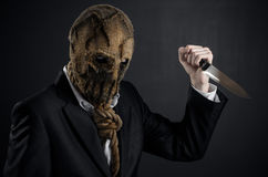 Fear and Halloween theme: a brutal killer in a mask holding a knife on a dark background in the studio Stock Photo