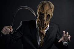 Fear and Halloween theme: a brutal killer in a mask holding a sickle old on a dark background in the studio Stock Photo
