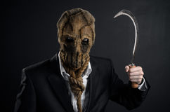Fear and Halloween theme: a brutal killer in a mask holding a sickle old on a dark background in the studio. Fear and Halloween theme: a brutal killer in a mask stock image