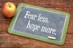 Fear less, hope more. Words of wisdom on a slate blackboard against red barn wood stock photos