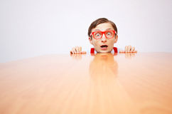 Fear in the office. Funny nerd hiding behind a desk Stock Photos