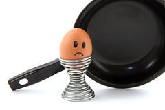 Fear and sad about your fate. Egg in egg holder in front of frying pan looking sad Royalty Free Stock Photos