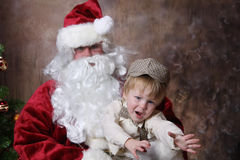 Fear of Santa. Young toddler reaching out for help while on santas lap stock photo