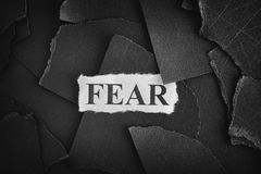 Fear. Torn pieces of black paper and word Fear royalty free stock image