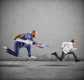 Fear of the vaccine concept with running child. Fear of the vaccine concept with running kid pursued by a doctor Stock Images