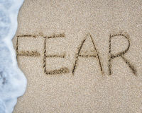 Fear word hand written with wave foam on sand beach Royalty Free Stock Image