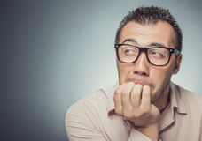 Fear and worry. Man biting nails in fear. Close up of a funny businessman over gray background stock images