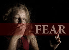 Fear written on virtual screen. hand of frightened young girl melancholy and sad at the window in the rain. Royalty Free Stock Photos