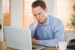 Fearful businessman looking at his laptop Stock Photography