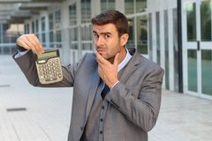 Fearful businessman showing a calculator with space for copy.  royalty free stock photo