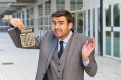 Fearful businessman showing a calculator with space for copy.  stock photos
