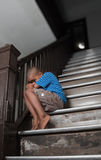 Fearful child. Sitting on a wooden staircase Royalty Free Stock Image