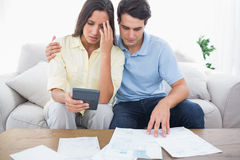 Fearful couple doing their accounts. Sat on a couch stock image