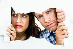 Fearful couple peeking. Through torn white paper stock image