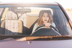 Fearful driving woman, learns to drive automobile, attractive female sits at wheel alone for first time, tries to avoid car. Accident, has frightened facial royalty free stock image