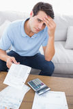 Fearful man doing his accounts with a calculator. Sat on a couch royalty free stock photography