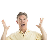 Fearful Man Gesturing While Looking Away. Fearful mature man gesturing while looking away against white background Stock Photography