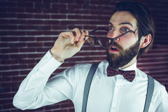 Fearful man holding eyeglases. While looking away against brick wall royalty free stock photo