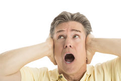 Fearful Man Looking Up While Covering His Ears. Close-up of fearful mature man looking up while covering his ears against white background Royalty Free Stock Photo