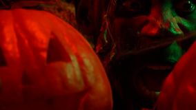 Scream of terror by the scary man behind halloween pumpkins, close up. Fearful man opens his eyes among carved pumpkins, and starts screaming and moving his jaw stock video footage