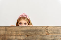 Fearful princess peeping over board Royalty Free Stock Photography