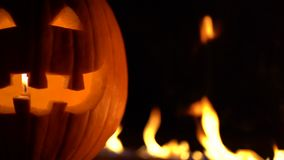 Fearful symbol of Halloween - Jack-o-lantern. Scary smiling head of pumpkin in inferno fire flames. Half of orange gourd. On the left side. Glowing face, trick stock video