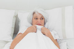 Fearful woman clutching her quilt. In bed royalty free stock photography