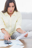 Fearful woman doing her accounts. Sat on a couch royalty free stock image